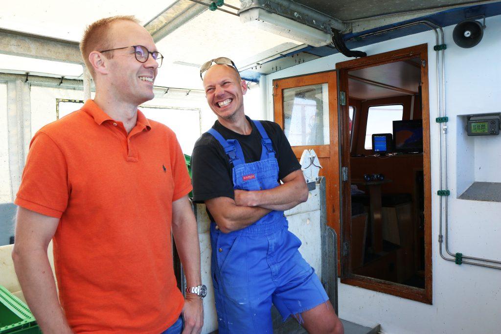 """Glade lakser på jakt etter torsk: Restauratør Jakob Sund (til venstre) og fisker Lars Lundholm ombord i fiskeskøyta """"Pedit""""."""